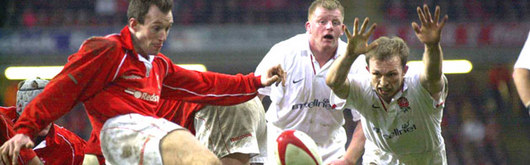 Rob Howley takes on his England counterpart Matt Dawson as Wales pressured England to start