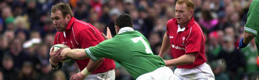 Scott Quinnell, flanked by Martyn Williams attempts to break into Irish territory