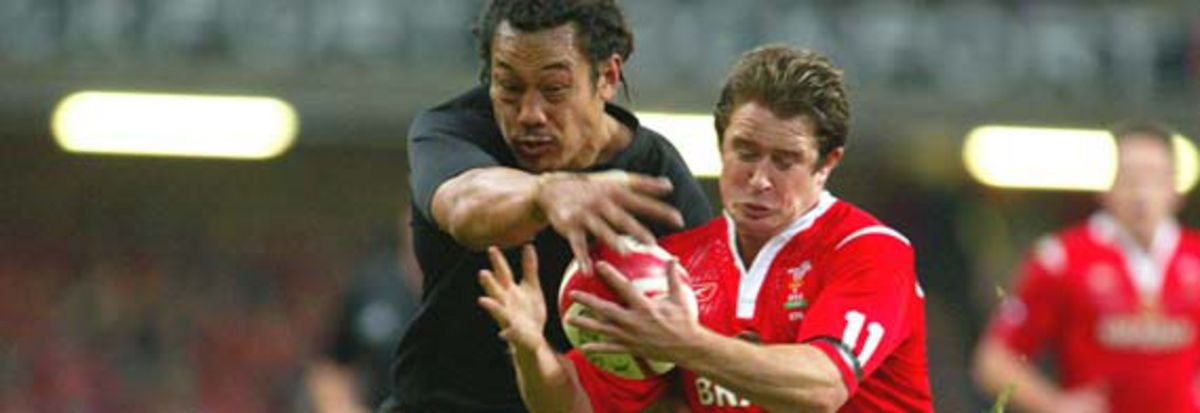 New Zealand Captain Tana Umaga wrestles the ball from Shane Williams