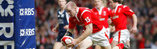 Gareth Thomas grounds the first of his brace of tries after a clever chip over the retreating Scottish defence