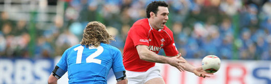 Stephen Jones evades the clutches of Mirco Bergamasco in last season's RBS Six Nations clash at the Stadio Flaminio