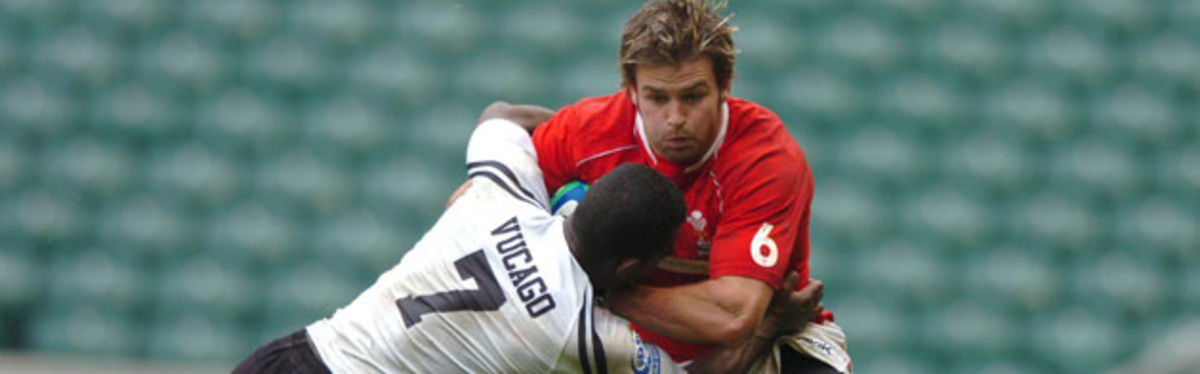 Tal Selley holds off Emosi Vucago in Wales's semi-final loss to Fiji at Twickenham