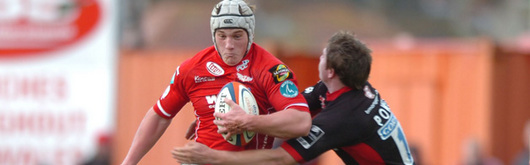 Scarlets' try scorer Jonathan Davies takes on Adam Powell in the EDF Energy Cup tie