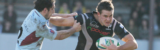 Ospreys' try-scorer Lee Byrne shrugs off Bourgoin's Sebastien Laloo in the Heineken Cup clash at the Stade Pierre Rajon