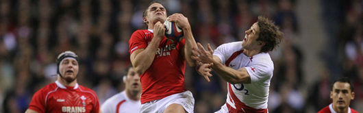Wales try-scorer Lee Byrne contests a high ball with England scrum half Andy Gomarsall