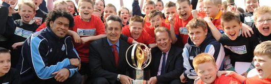 Blues stars Maama Molitika and Ben Blair, Nigel Davies and Rhodri Glyn Thomas with children from St Fagans and Trelai schools with the Junior World Championship Trophy